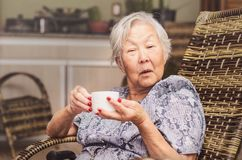 Old lady holding a cup of tea with a surprised expression. Portrait of a old lady japanese descendant seated comfortably at home holding a cup of tea with a Royalty Free Stock Photography