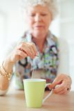 Old Lady Holding a Tea Bag. Old lady sitting at home holding and dipping a tea bag Royalty Free Stock Photo