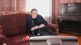 Old lady at home - senior woman watching television and knits wool socks. Middle shot Stock Images