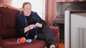 Old lady home at sofa - senior woman watching television and knits wool socks. Middle shot Stock Photos