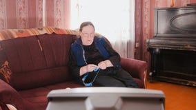 Old lady home at sofa - senior woman watching television and knits wool socks. Middle shot Royalty Free Stock Photos