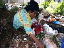 An old lady hunts or scavenges for recyclable materials in a pile of trash in an abandoned lot. Stock Image