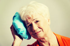 An old lady with ice bag by her head Royalty Free Stock Image