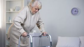 Old lady learning to walk with frame, rehabilitation after hip joint replacement