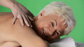 An old lady lying at spa salon. An old lady lying at spa salon having massage. On green background stock video