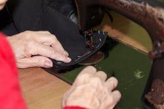 Old lady machine sews stock photography