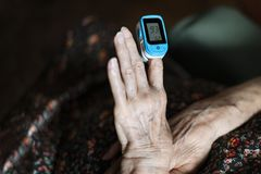 Old lady measuring her oxygen saturation with a pulse oximeter. Health concept royalty free stock photography