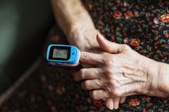 Old lady measuring her oxygen saturation with a pulse oximeter stock photo