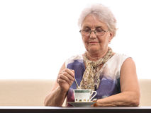 Old lady mixing in coffee cup Royalty Free Stock Images