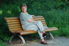 Old lady on park bench. Old woman on park bench in afternoon sun smiling Royalty Free Stock Photography