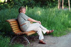 Old lady on park bench. Old woman thinking on park bench in afternoon sun Stock Photography