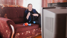Old lady pensioner at home in glasses knitting in front of the TV Stock Photo