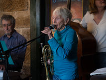 Old lady playing trumpet in a band close up. A 90 year old musician plays trumpet with a band in an old pub in the Rocks, Sydney Stock Image