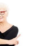An old lady pointing on copy space. Cut out. Stock Photo