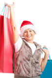 An old lady with presents and santa hat. Stock Photo
