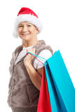 An old lady with presents and santa hat. Royalty Free Stock Photography