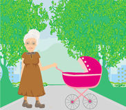Old lady pushing a stroller in the park Stock Photos