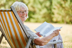 Old lady reading a book and smiling. Old happy lady reading a book and smiling in summer in the nature Royalty Free Stock Photo