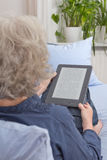 Old lady reading digital book Royalty Free Stock Photography