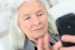 Free Old Lady Reads Smart Phone Stock Photo - 103879700