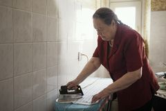 Old lady in the red blouse ironing a towel Royalty Free Stock Photography