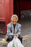 Old lady red wall. BEIJING, CHINA-26th MARCH 2014:-The old lady is resting beside a red wall outside the forbidden city Stock Photo