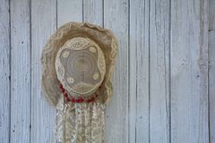 Old lady`s hat hangs on the left of wooden wall stock photo