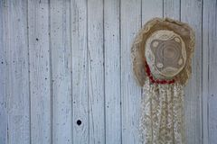 Old lady`s hat hangs on the right of wooden wall royalty free stock photography
