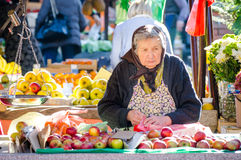 Old lady sales apples and flowers at the market place. Royalty Free Stock Photography