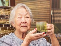 Old lady seated comfortably at home holding a cup of black coffe. E Stock Photos