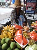 Old lady selling fruit, Thailand. PATTAYA, THAILAND - DECEMBER 24 : Thai old lady walks and sells fresh cut fruit from baskets. December 24, 2005 in Pattaya Stock Images