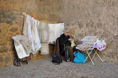 Old lady selling laces. An old lady selling beautiful laces in the street royalty free stock image
