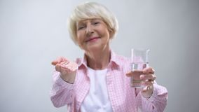Old lady showing pills and glass of water at camera, pharmacology and healthcare