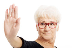 An old lady showing stop sign by hand. Stock Photography