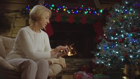 Old lady surfing the Internet smartphone by Christmas tree. Old lady sitting alone with smartphone and surfing the Internet by Christmas tree stock footage