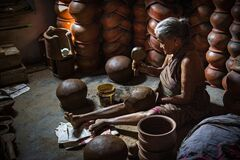 An old lady sitting inside her home making mud pot in her home