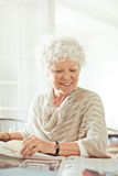 Old Lady Smiling While Reading the News Stock Image