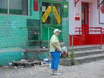 An old lady is standing in front of retail supermarket. Yaroslavl, Russia stock photo