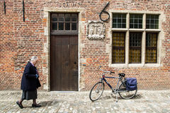 Old lady on the streets of Beguinage. Old lady passes wooden door and parked bicycle in Grand Beguinage of Leuven, Belgium. Grand Beguinage of Leuven is included stock image