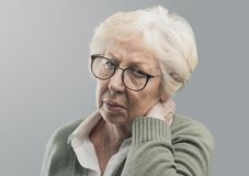 Old lady suffering with neck pain. She is touching her neck, healthcare and aging concept royalty free stock photo