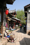 An old lady takes a nap on the cobblestone streets of Lijiang Old Town Royalty Free Stock Image