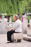 Old lady takes some rest near Houhai Lake, Beijing, China Stock Photo