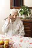 The old lady talking on a cell phone while sitting at a table in the living room. Hands of an old woman holding a mobile phone Royalty Free Stock Images