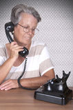 Old lady talking on old phone Royalty Free Stock Images