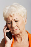 An old lady talking through phone. She is receiving bad news. Over grey background Royalty Free Stock Images