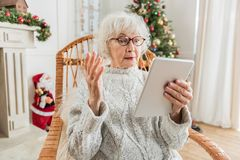 Old lady is using modern gadget in holiday Stock Photography