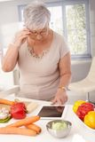 Old lady using tablet in kitchen Stock Photos