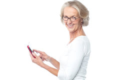 Old lady using tablet pc device. Aged lady operating touch pad device Royalty Free Stock Image