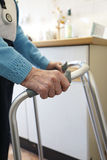 Old lady using a walking frame. Pensioner using a walking frame for stability Stock Photo