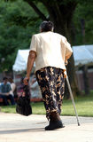 Old Lady Walking. Up a hill with a cane stock photos